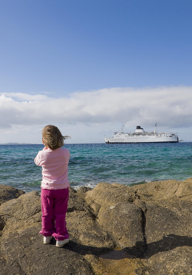 A small child on the shore watching a ship at sea.  royalty free stock photo