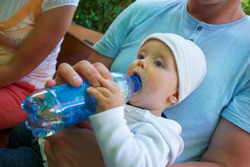 A small child sits and drinks water royalty free stock photography