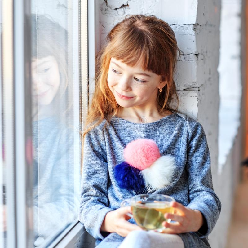 A small child sits on a window sill and looking out the window. stock images