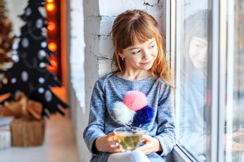 A small child sits on a window sill and looking out the window stock image