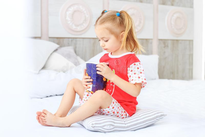 A small child sitting on the bed in his pajamas. The concept of stock photography
