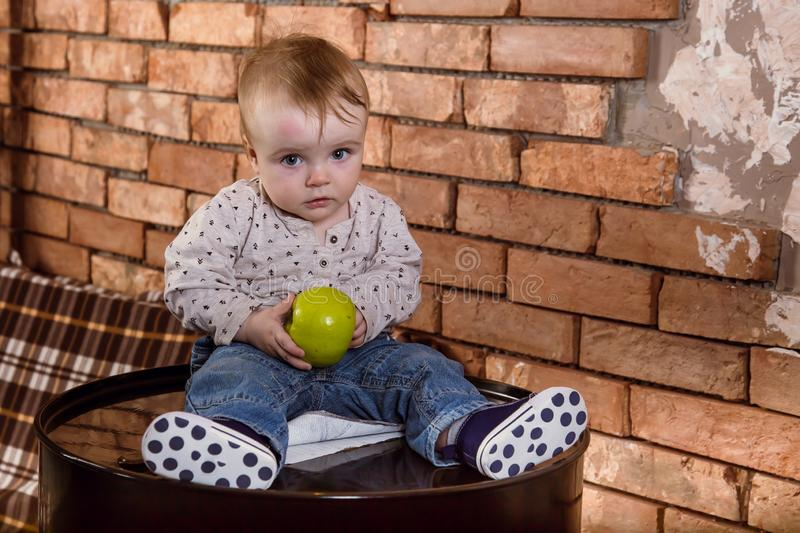 A small child is sitting on a iron barrel and holding an apple in his hands. Baby boy with fruit on background of red brick wall. Industrial loft kid green stock images