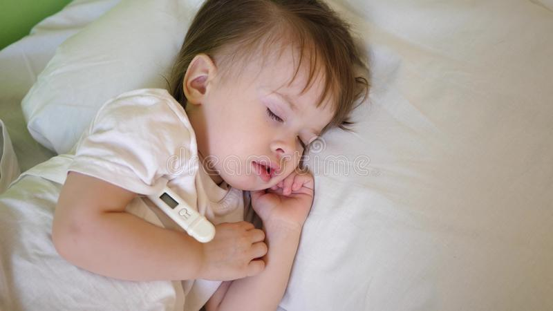 Small child sleeps in hospital ward on white bedding and measures temperature with thermometer. Treatment of children in stock images