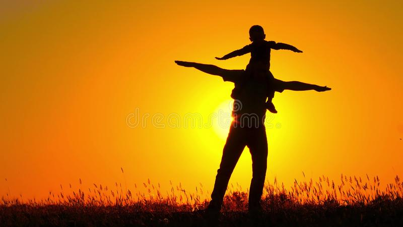 A small child spinning on his father`s shoulders. Happy family playing at sunset. Silhouette. 4k royalty free stock image