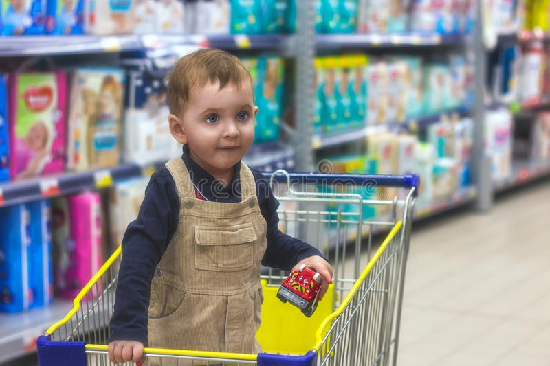 Small child is standing in a grocery cart in the store and choosing toys. stock photography