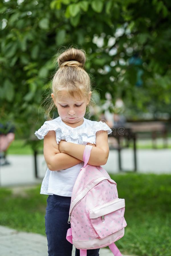 A small child stands offended on the street with a backpack. The concept of school, study, education, childhood.  royalty free stock image