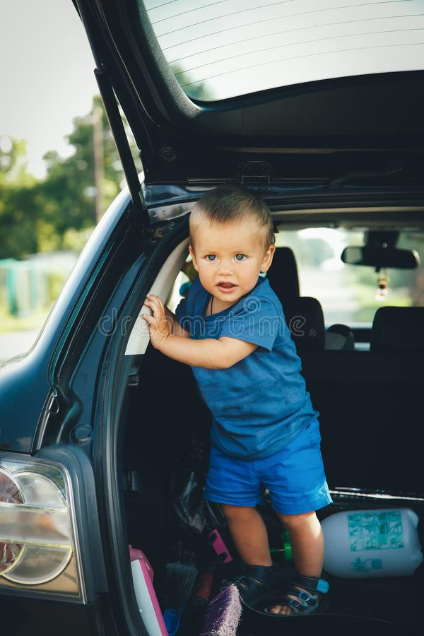 A small child stands in the trunk of the car plays and laughs royalty free stock photos