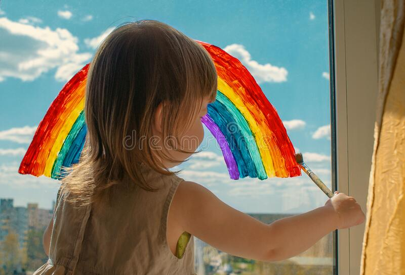 A small child stands on the windowsill and draws a rainbow on the window glass. multi-colored rainbow. symbol of happiness. select. Ive focus royalty free stock photos