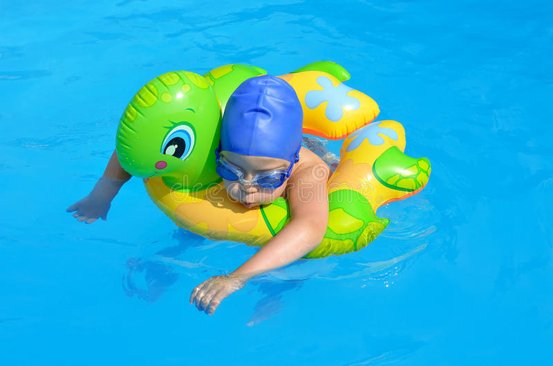 A small child swims in the pool, goggles, swim cap. Happy little girl in a swimming pool royalty free stock photography