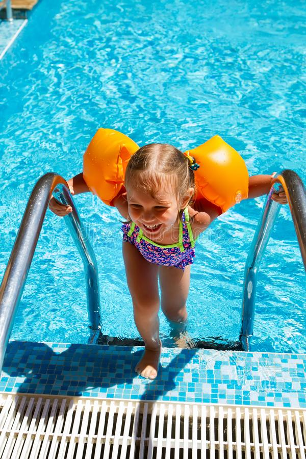 Small child tries to climb out of the pool. stock image