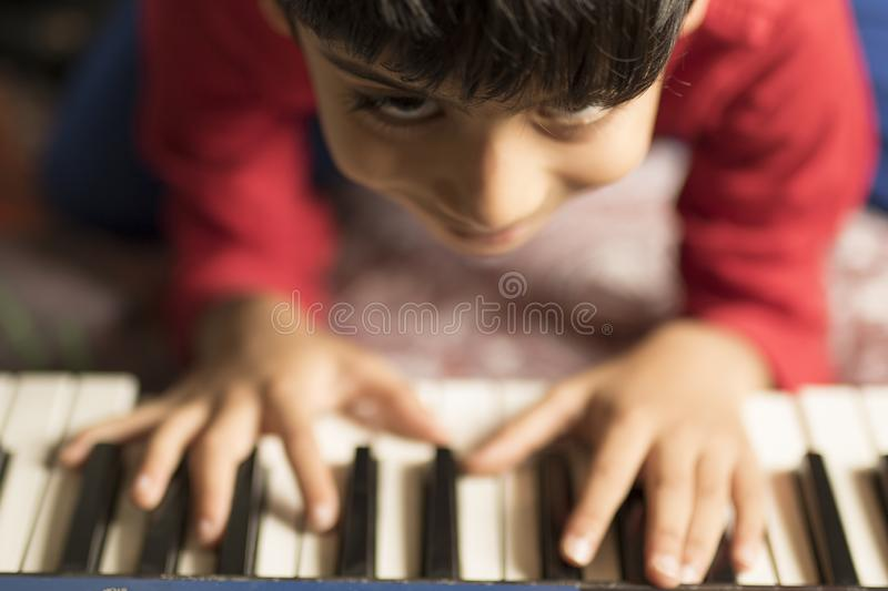 A small child is trying to play piano. In a joyful mood royalty free stock photo