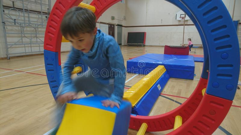 A little boy balancing on a gymnastics beam thinking of his next move. A small child walking clambouring climbing along a soft play padded foam play equipment stock images