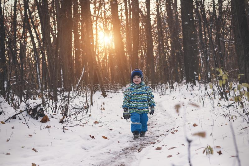 Small child walking on a snowy path among gloomy forest. stock image