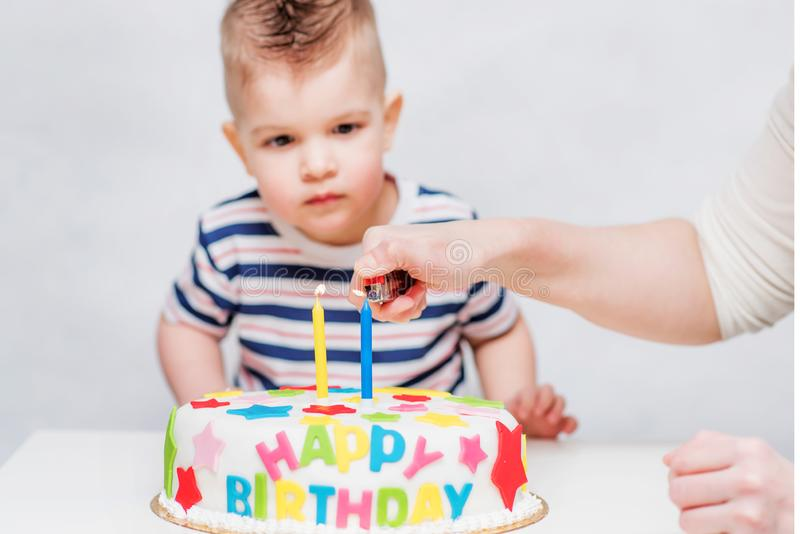 Little baby watches his mom light candles on the cake royalty free stock photography