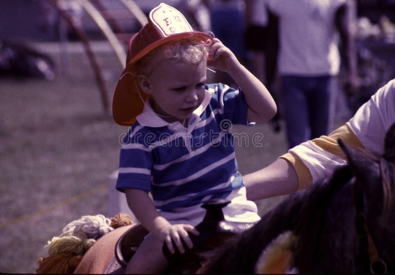 Small child wearing a fireman`s helmet stock images