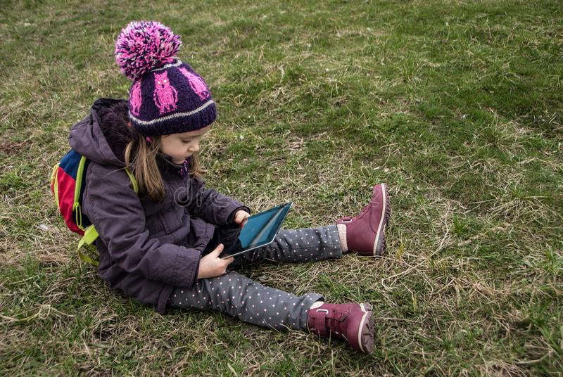 Small childgirl sitting on a grass and watching digital device royalty free stock photography