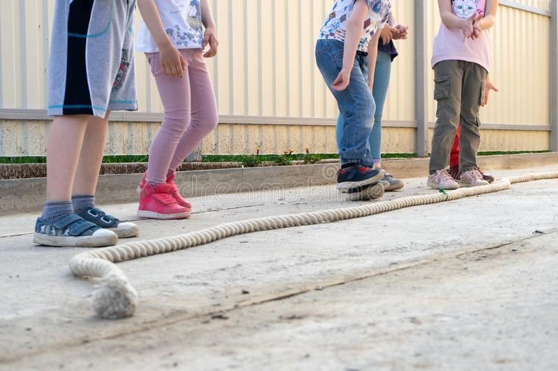 Small children boys and girls playing games - jump over the rope getting ready to jump. Perspective on the legs stock photo