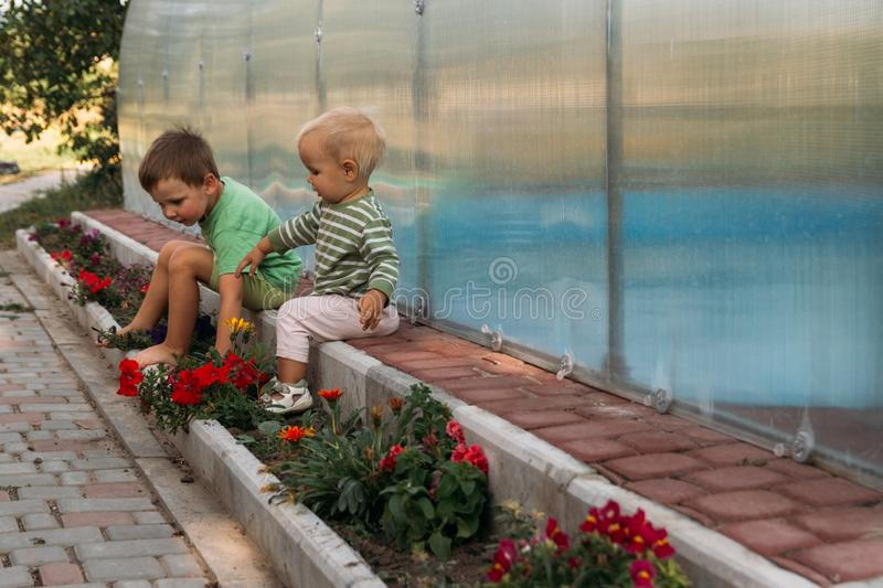 Small children, a boys, sit on a path near a club, barefoot, behind them a covered pool, greenhouse, summer, spring in the village royalty free stock images