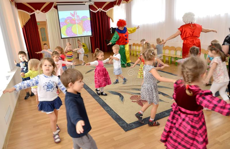 Small children dance together with clowns-animators. A holiday in kindergarten royalty free stock image