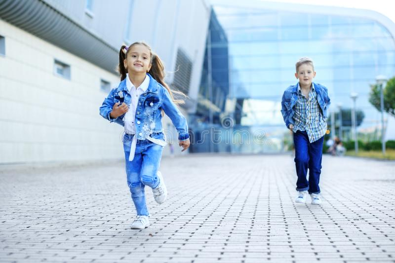Small children run down the street. The concept of childhood, family, education. And school royalty free stock image