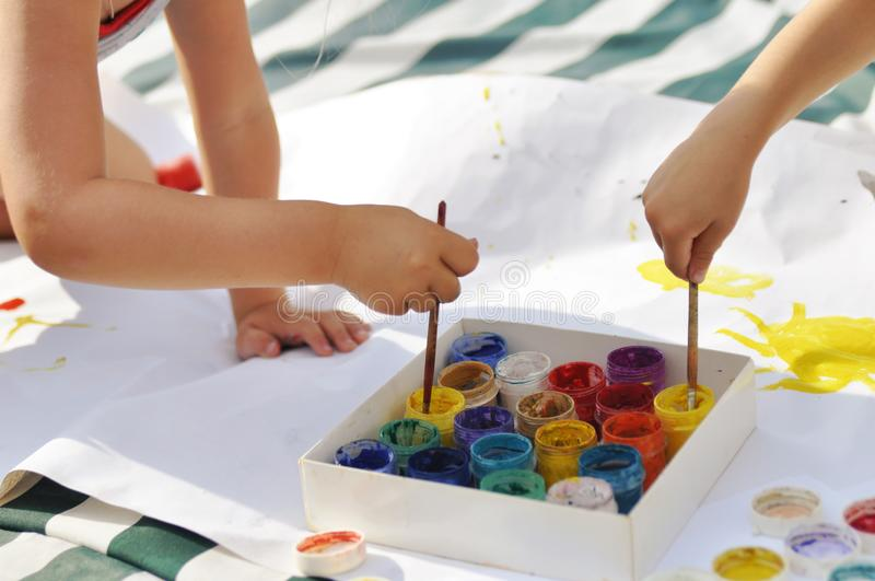 Small children`s hands paint with paints and brushes on a large sheet on the street on a Sunny day, creativity and fun. Art, sun stock photos