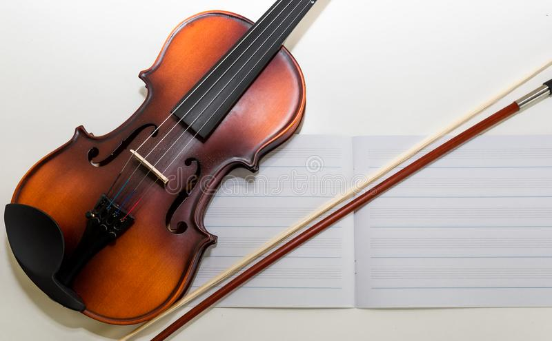 A Small Children`s Violin and Bow on a Child`s Study Desk. Colorful letters / magnets in the background. A set-up for teaching children to play the violin stock photo