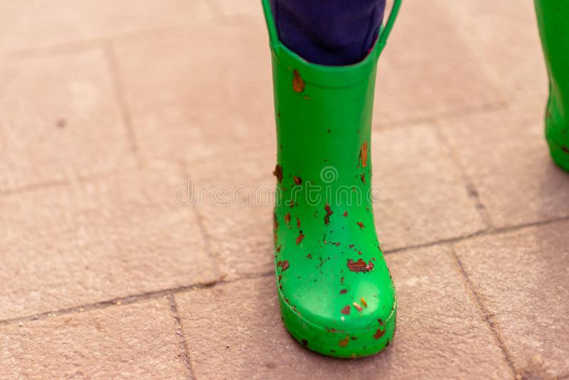 Small childs green welly covered in dirt and leaves royalty free stock image