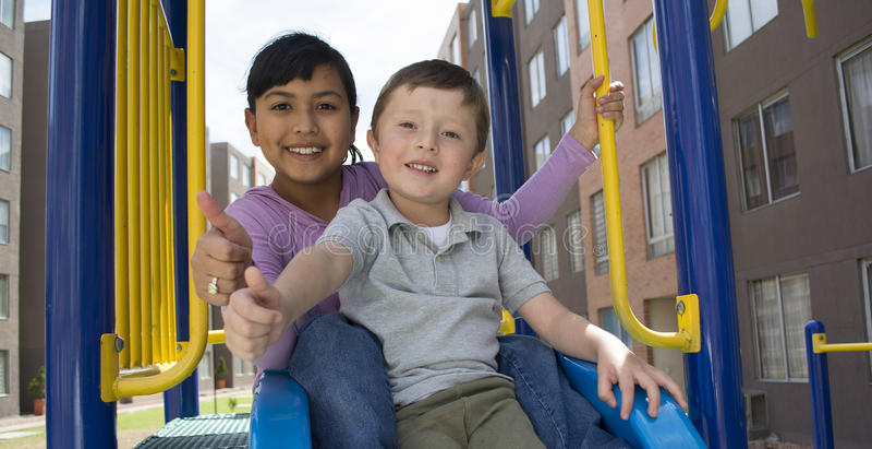 Small childs on slide. Small childs on slide in an outdoors playground stock photos