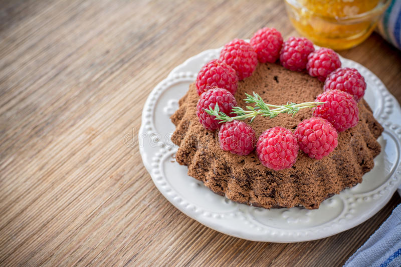 Small chocolate cake. Small homemade chocolate cake with fresh raspberries sprinkled with cocoa powder on wooden background with honey. selective Focus stock photo