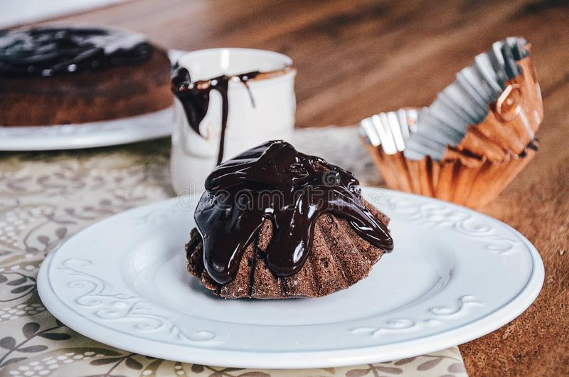 Small chocolate cake with large portion of chocolate glaze. Two copper muffin baking forms on background royalty free stock images