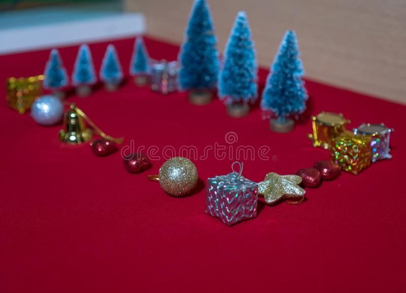 Small Christmas decorations resting on the red carpet royalty free stock image