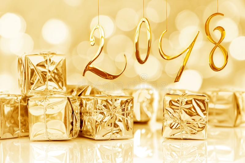 2018, small Christmas gifts in shiny golden paper, bokeh lights background stock images