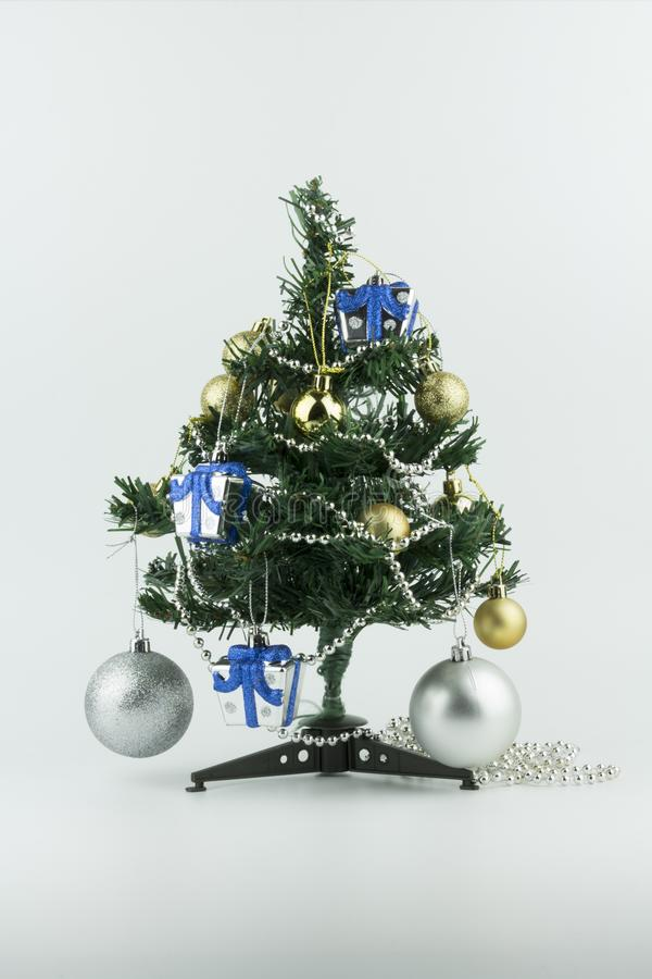 Small Christmas tree is decorated with ornaments such as ball and gift, isolated on white background. Small Christmas tree is decorated with ornaments, isolated stock photo