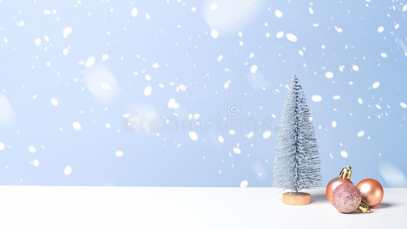 Small Christmas tree with pink balls in snow on blue background. Christmas banner with copy space, New Year greeting card template royalty free stock photo