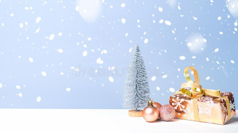 Small Christmas tree with present and balls in snow on blue background. Christmas banner with copy space, New Year greeting card stock photography