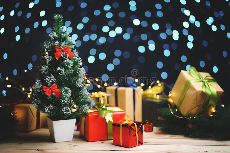 Small Christmas Tree Between Christmas Presents Against Beautifull Blue Lights Bokeh royalty free stock image