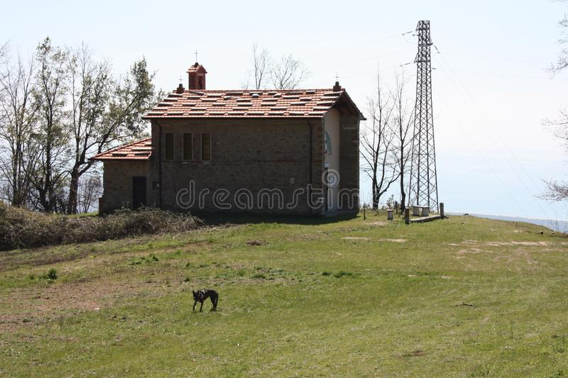 Small church abandoned, in disuse, on the Apuan Alps of the Tuscan Apennines in a clearing on a sunny spring day.  royalty free stock photography