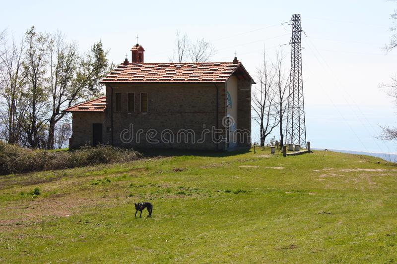 Small church abandoned, in disuse, on the Apuan Alps of the Tuscan Apennines in a clearing on a sunny spring day.  stock photo