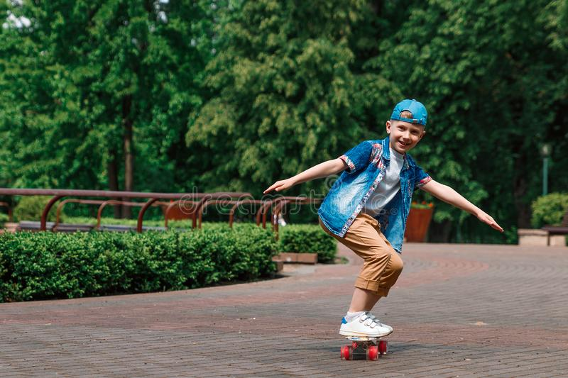 A small city boy and a skateboard. A young guy is riding in a park on a skateboard. City Style. City children. A child learns to royalty free stock images