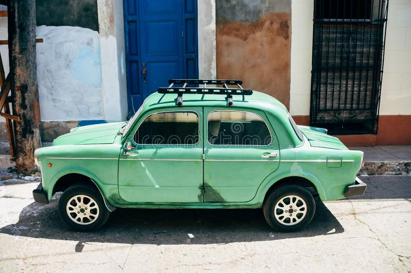 A small classic import parked in Trinidad, Cuba. A small classic light green import car parked in Trinidad, Cuba royalty free stock images