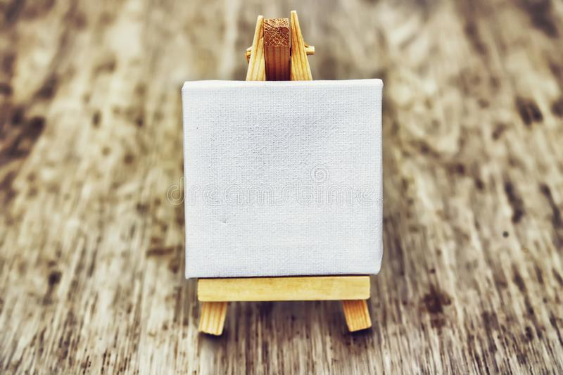 Small clean easel on wooden background. Abstraction for thoughts and ideas. White easel. Small clean easel on wooden background. Abstraction for thoughts and stock photos