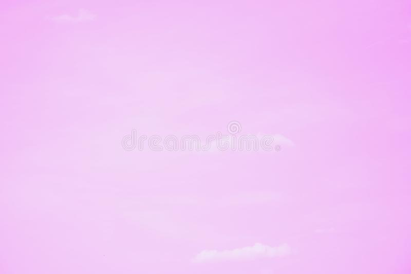 Small clouds on a clear pink sky background. Copy space stock image