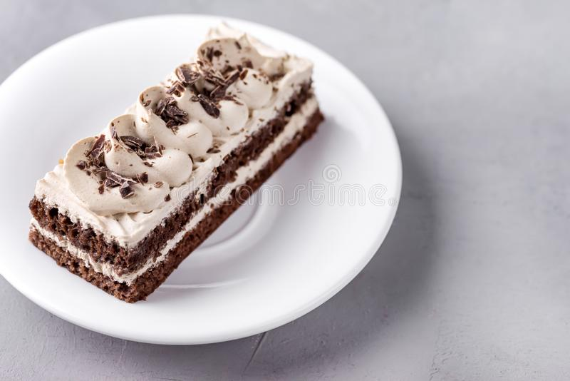 Small Coffee Chocolate Cake on White Plate Grey Background Tasty Beautiful Dessert Chocolate Cake Pastry Close Up Copy Space.  stock image