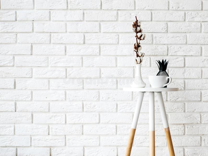 Small coffee table with cup and decor on the white brick wall ba royalty free stock photography