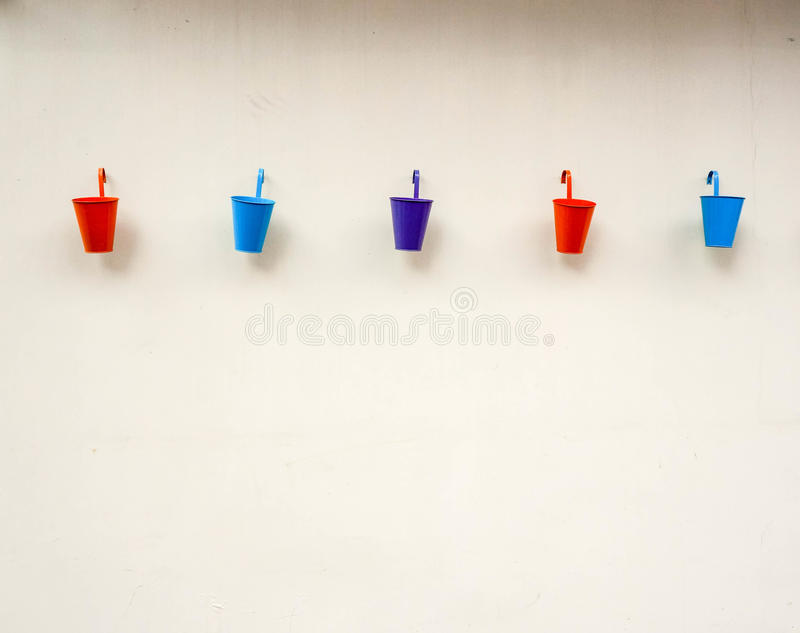 Small color buckets on wall background. Small color buckets on white wall background royalty free stock images
