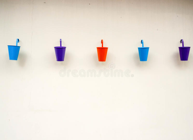Small color buckets on wall background. Small color buckets on white wall background royalty free stock photo