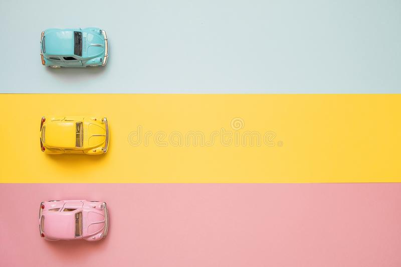 Small color toy cars at the start on a yellow, pink and blue background. Racing cars on a table top racetrack. Concept for competition or childhood. Business royalty free stock image