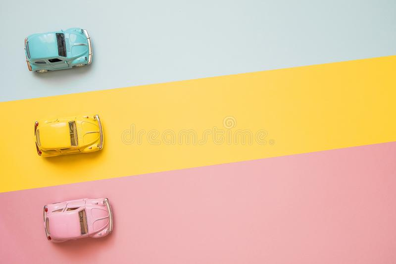 Small color toy cars at the start on a yellow, pink and blue background. Racing cars on a table top racetrack. Concept for competition or childhood. Business royalty free stock photography