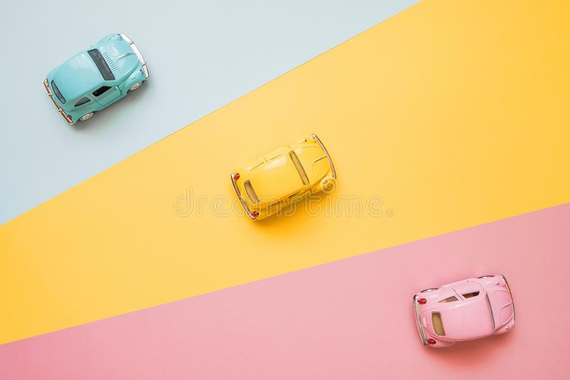 Small color toy cars on a yellow, pink and blue background. Business competition, winners and losers. Finish line. Small color toy cars on a yellow, pink and royalty free stock image