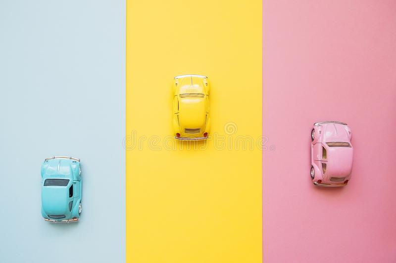 Small color toy cars on a yellow, pink and blue background. Business competition, winners and losers. Finish line. Small color toy cars on a yellow, pink and royalty free stock photography